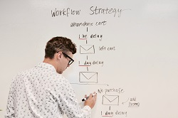 Man writing at a white board.