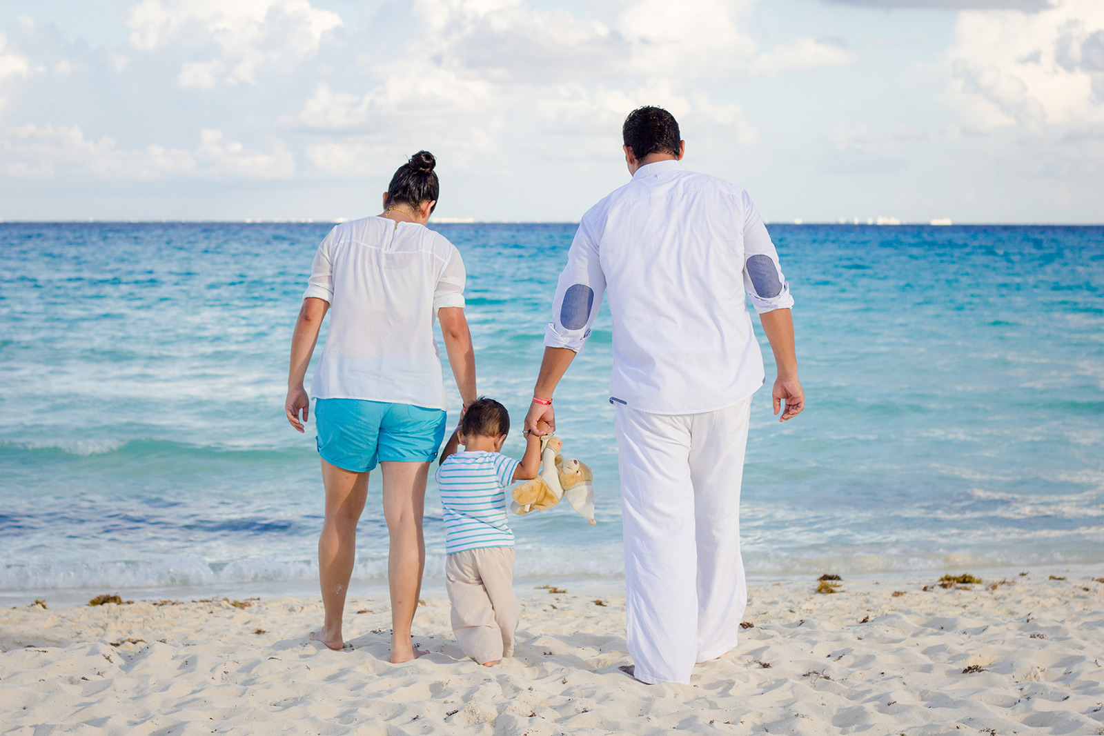 Mother, father, and child walking on beach